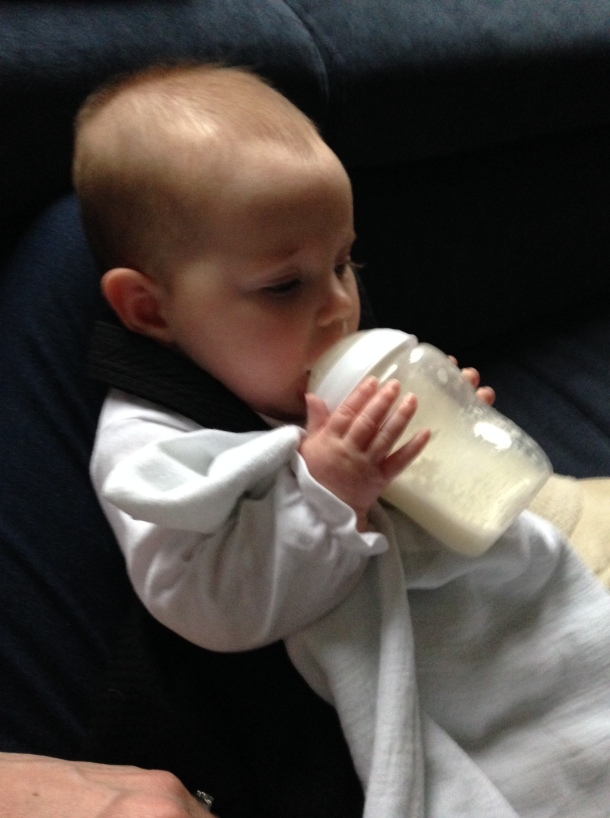 6 month baby holding bottle